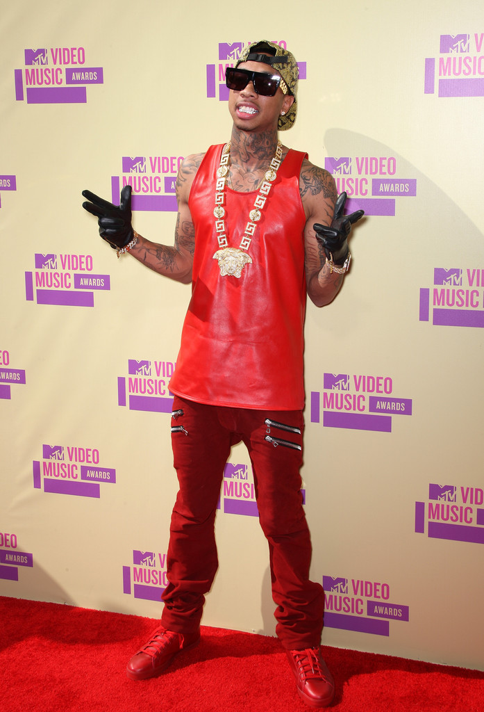 Tyga-supreme-snakeskin-hat-Celine-gold-chain-sunglasses-red-leather-tank-top-Balmain-jeans-red-sneakers-Upscalehype