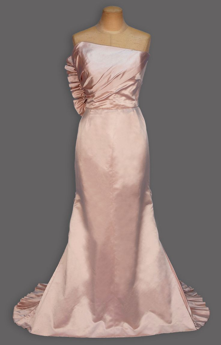 1940's. Dusty pink silk having asymmetrical semi boned bodice with diagonal drape ruched into side seam, trained skirt with three pleated gores and lower back