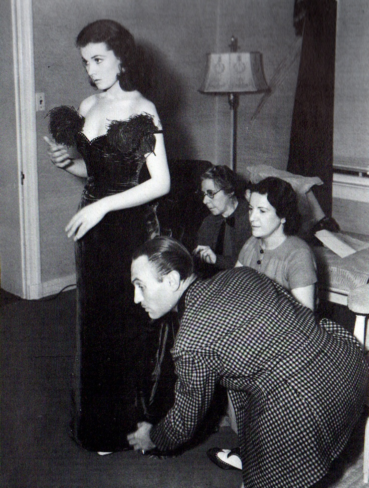 Walter Plunkett (costumer for Gone with the Wind) fitting Vivien Leigh in a sport jacket. Note that the armholes have gussets, and that the back has a yoke, a belt, and pleats in the skirt. This is the kind of jacket you need if you are going to be squatting in your sport jacket.