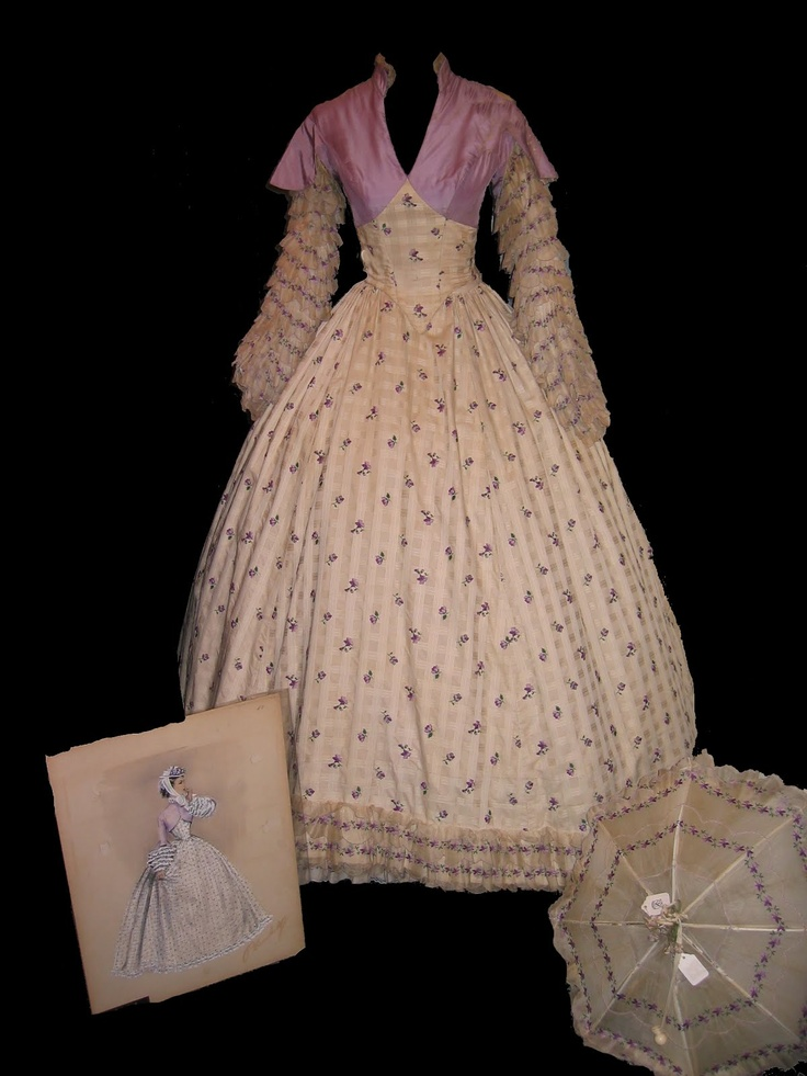 Here is a full-length gown designed by Walter Plunkett and worn by Elizabeth Taylor in the 1957 MGM film Raintree County. The bodice of mauve taffeta with full sleeves of layers of tulle embroidered with mauve flower heads, the full-length skirt of ivory cotton embroidered all over with mauve flower heads, with corresponding layered underskirt; and a parasol -- made for Elizabeth Taylor as Susanna Drake in the movie.