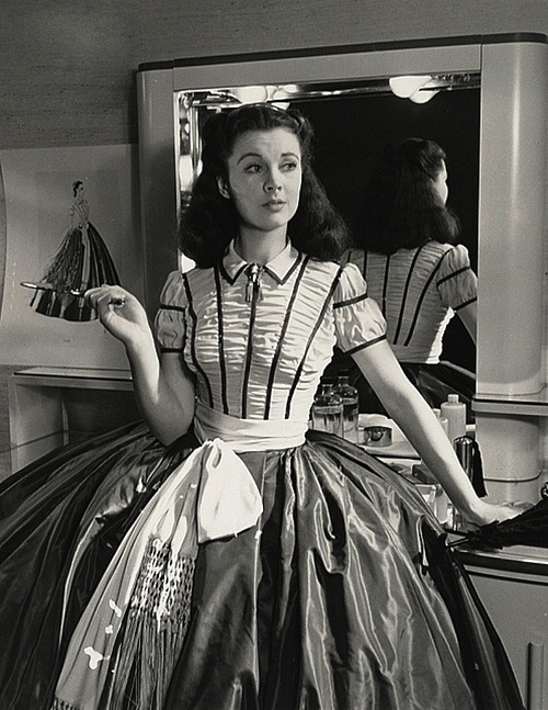 "Vivien Leigh behind the scenes of ""Gone with the Wind."" One of Walter Plunkett's costume sketches is visible to the left."