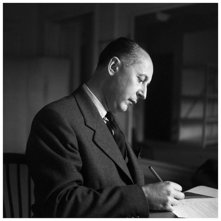 1950 --- Christian Dior Writing at Desk --- Image by © Bettmann/CORBIS