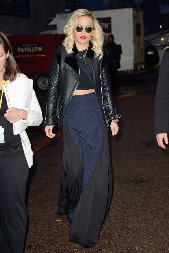 Rita Ora is rocking a navy and black maxi skirt with a crop top and a quilted leather bomber jacket.