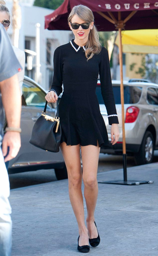 Taylor Swift rocking a black long sleeved mini dress with flat shoes