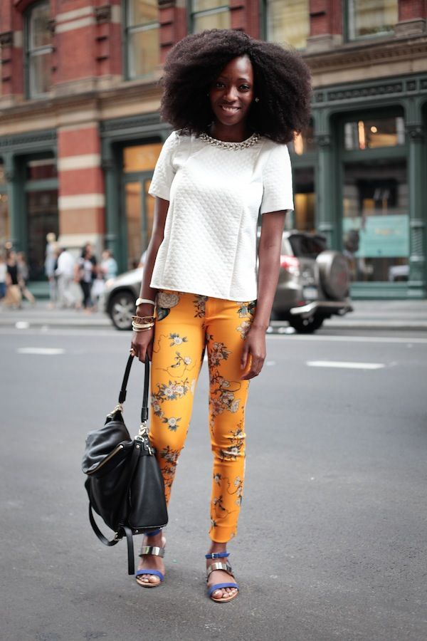 White blouse, yellow floral pants , Afro, purple and gold sandals and black bag