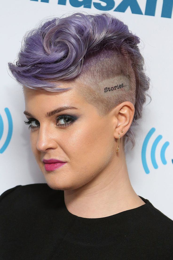 Kelly Osbourne rocking a lavender mohawk with her hair shaved and the word stories at the side of her hair