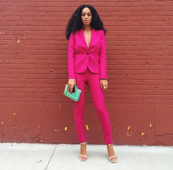 Solange Knowles is rocking a hot pink suit with green clutch