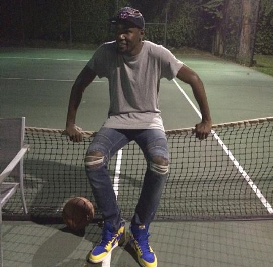 "Oklahoma City Thunder forward, Kevin Durant is rocking a an oversized grey tee-shirt with $1,056 Balmain 18cm Degrade' Knee Wash Denim Biker Jeans and Air Jordan 1 Retro High OG ""Laney"" sneakers."