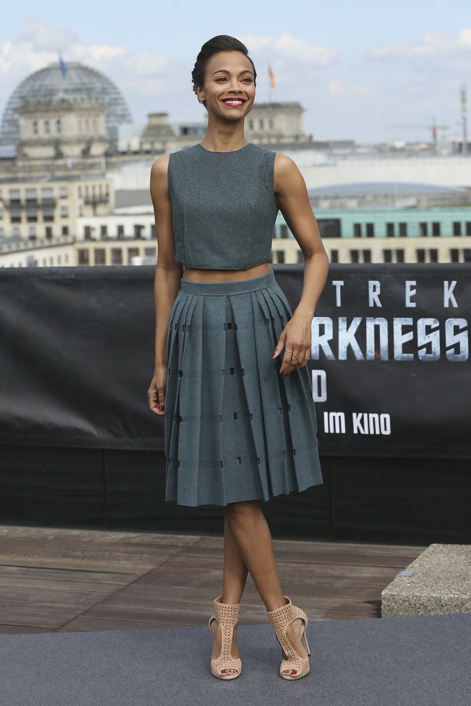 oe Saldana in a Calvin Klein gray grey crop top and grey and black pleated skirt