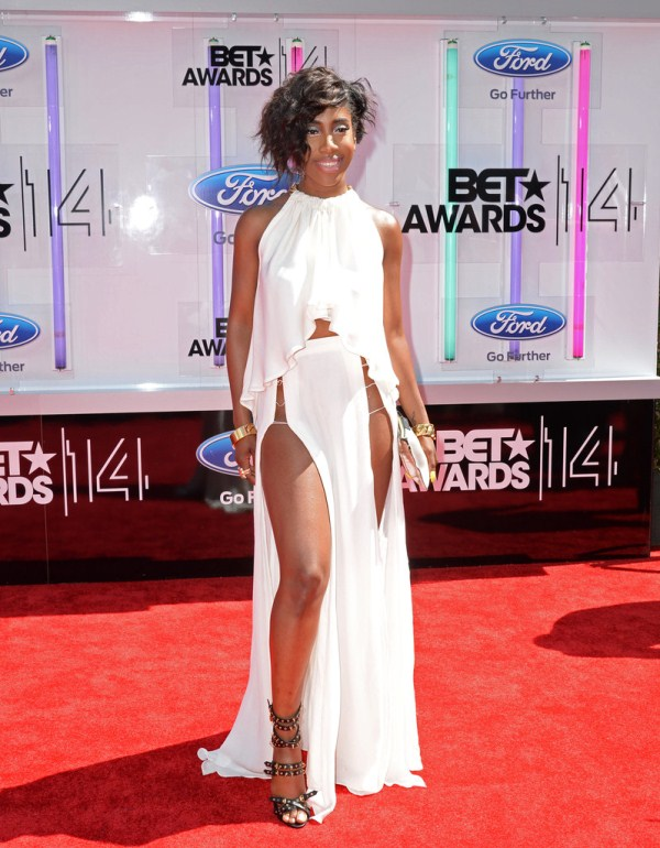 Sevyn Streeter is wearing a white flowing crop top with a asymmetrical skirt with slits in the middle of the leg
