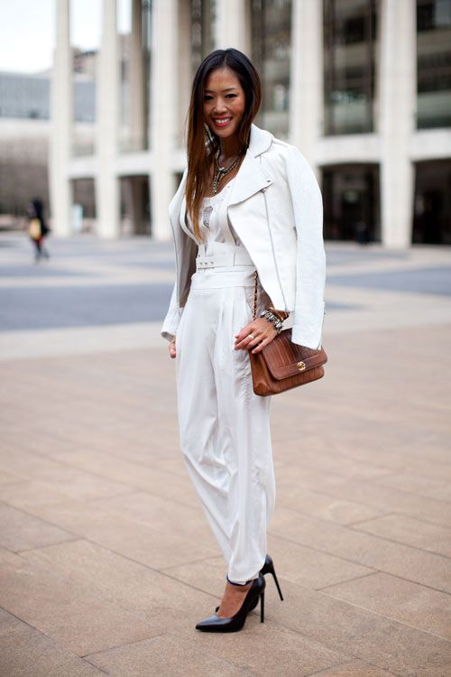 white Jacket worn over the shoulder , white top and pants with brown bag and black shoes
