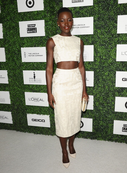 Lupita Nyong'o is wearing crop top and pencil skirt from Giambattista Valli's Spring 2014 collection with white point-toe pumps and a clutch