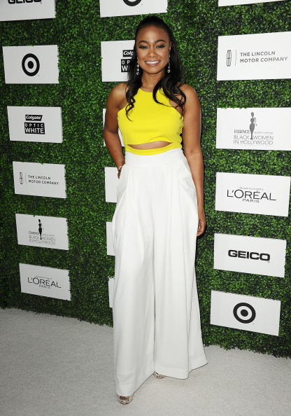 Tatyana Ali is rocking yellow crop top with a white palazzo pants.