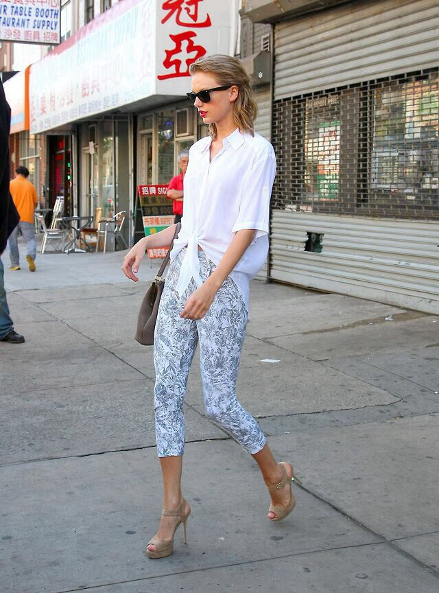 Taylor Swift rocking a white blouse, floral pants and nude shoes