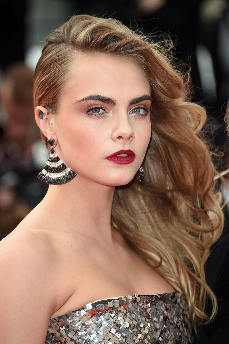 Cara Delevingne hair was swept to one sideat the Search premiere at Cannes.