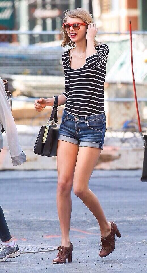 Taylor Swift rocking a black and white long sleeve shirt jeans shorts, red glasses, a vintage bag and brown shoes