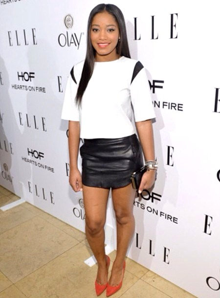 Keke Palmer is rocking a white and black leather top from Bec and Bridge, a black leather mini skirt from Mason by Michelle Mason, with a pair of red Stuart Weitzman pumps,