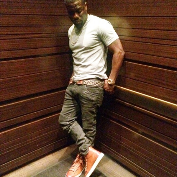 Comedian and Actor Kevin Hart is rocking a grey tee shirt with Balmain Biker Jeans. Goyard belt, and $990 Tom Ford Russell Leather High-Top Sneakers.