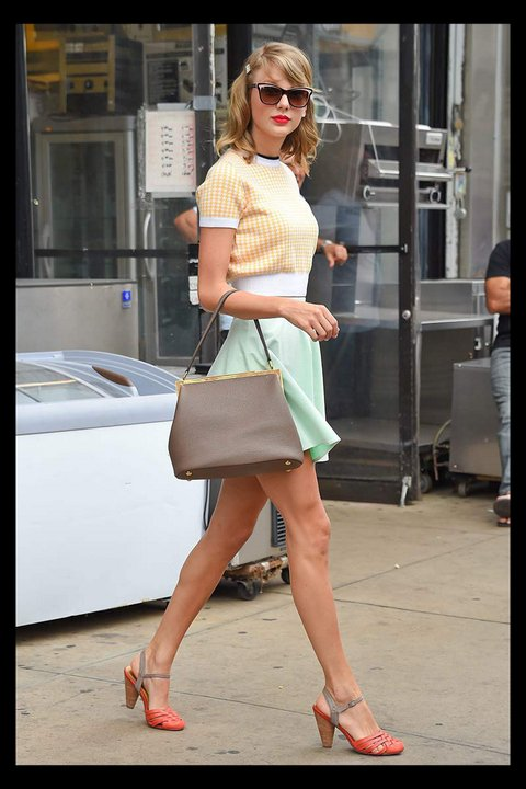 Taylor is rocking a yellow and white blouse with a green skirt , a antique bag ans antique looking shoes