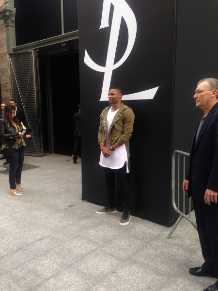 NBA star Russell Westbrook attended the Saint Laurent Spring/Summer 2015 Menswear rocking a $1,603 Saint Laurent Cotton Blend Gabardine Military Parka with a oversized white top, black skinny jeans and a pair of $715 YSL Malibu Leopard Calfhair Sneakers