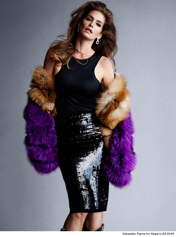 Cindy Crawford, 47 is wearing a black sequin mini knee length skirt , a black tank top, fishnet stockings and a purple and brown fur.
