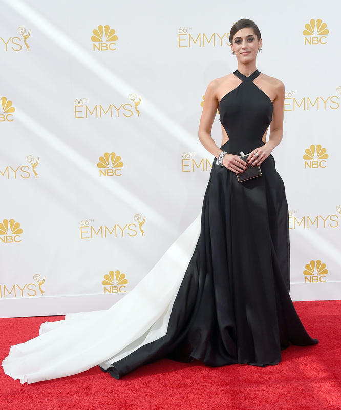 Lizzy Caplan in a black-and-white Donna Karan Atelier gown with cutouts ,sideswept hair, Neil Lane jewels, heels by Brian Atwood, and a clutch by Judith Leiber.