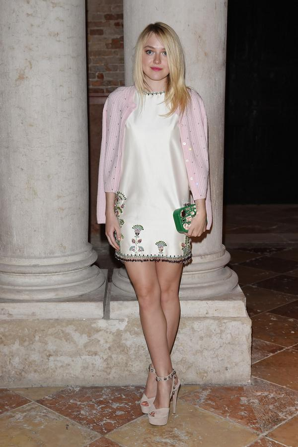 Dakota Fanning at the Miu Miu Women's Tales dinner in Venice wearing a pink cardigan with a white satin sheath dress that has beaded embellishment, paired with nude platform Miu Miu pumps and a bejeweled grass-green Miu Miu clutch.