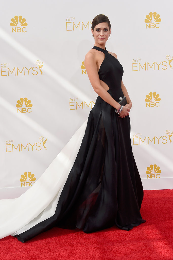 Lizzy Caplan in a black Donna Karan gown with a halter neckline, cut out at the sides and a train
