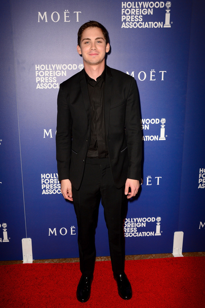 Logan Lerman wears a Dior Homme wool two-button small lapel suit with denim lining, a black cotton shirt and black leather derbies.