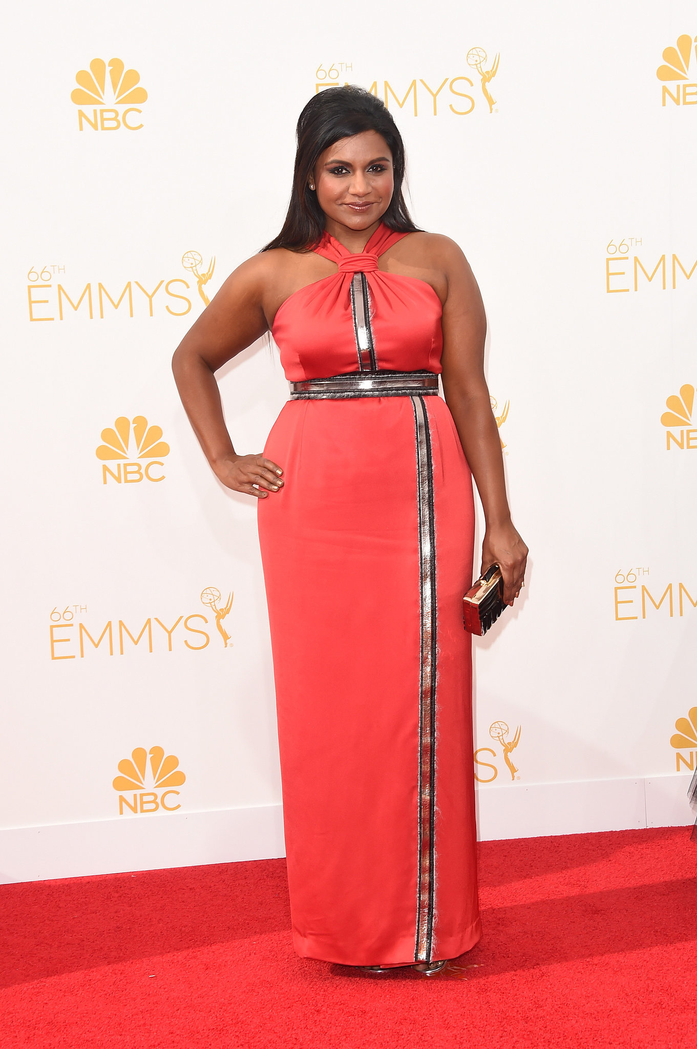 Mindy Kaling In Kenzo Halter tangerine dress with silver detailng at the waist , bustline and at front of the dress