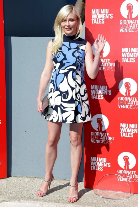 Kirsten Dunst in a sleeveless blue , white and black mini Miu Miu Dress with nude sandals.