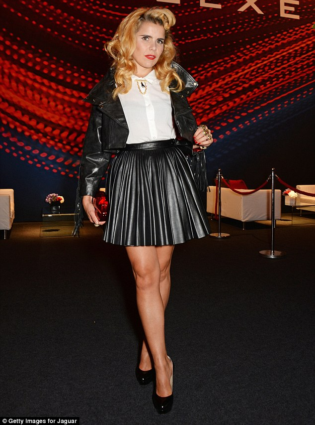 Paloma Faith in a white top with a black leather jacket and pleated skirt paired with black pumps at the Jaguar XE Event