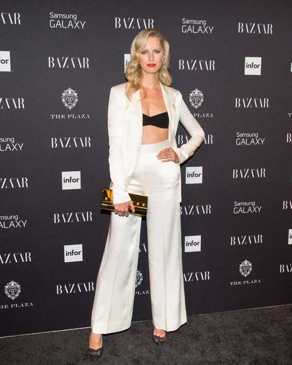 Model Karolina Kurkova in a a white satin The Row suit over a black bralette, worn with a gold Versace clutch, Tom Ford shoes and delicate Pamela Love and Anna Shefield jewels