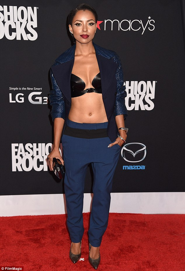Kat Graham in a navy blue dropped-crotch pants with black waistband, a black leather bra and dark blue shimmery blazer .