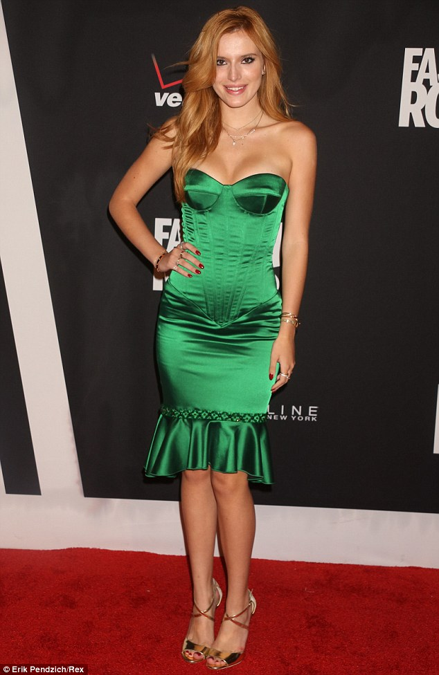 Bella Thorne is in an emerald satin dress with a ruffled hemline