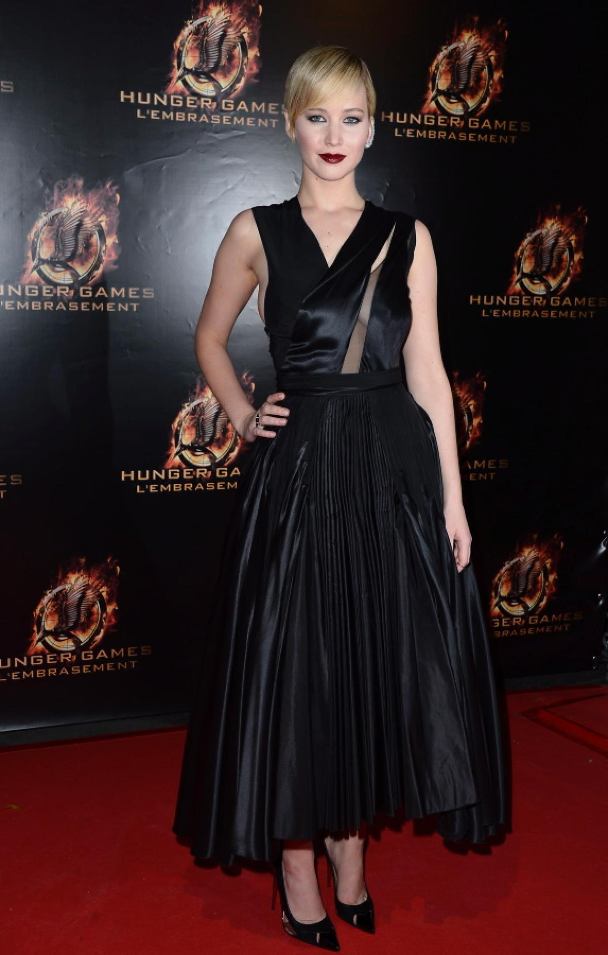 In a black satin Dior pleated dress at The Hunger Games Catching Fire Premiere in Paris on Nov . 15, 2013