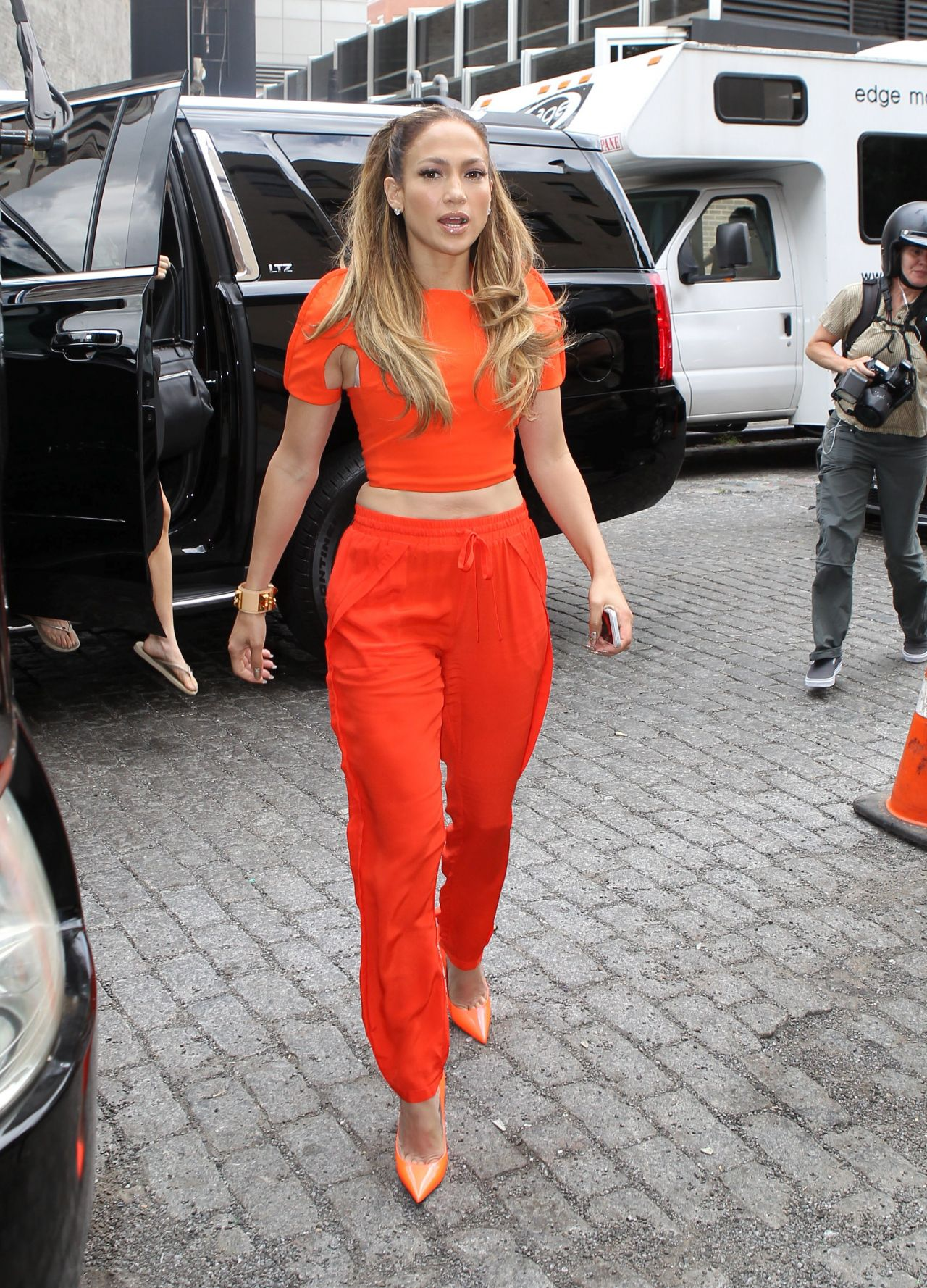 Jennifer Lopez Leaving Her Apartment wearing a orange crop top and pants in New York City – September 2014