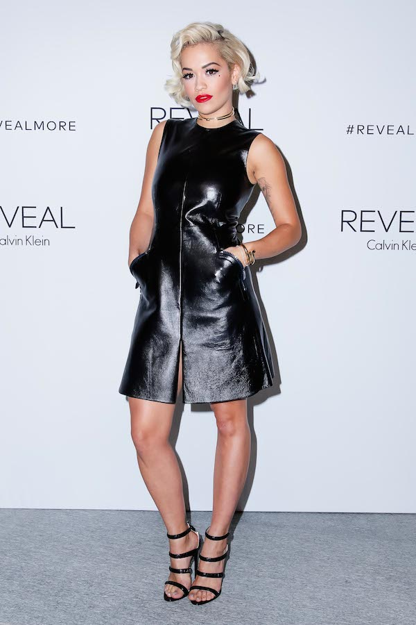 Rita Ora in a sleeveless black Calvin Klein Shift dress, red lips and black strappy shoes