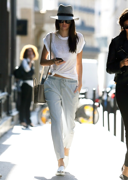 Kendall Jenner in a white t shirt, a grey and black fedora and tailored pants.