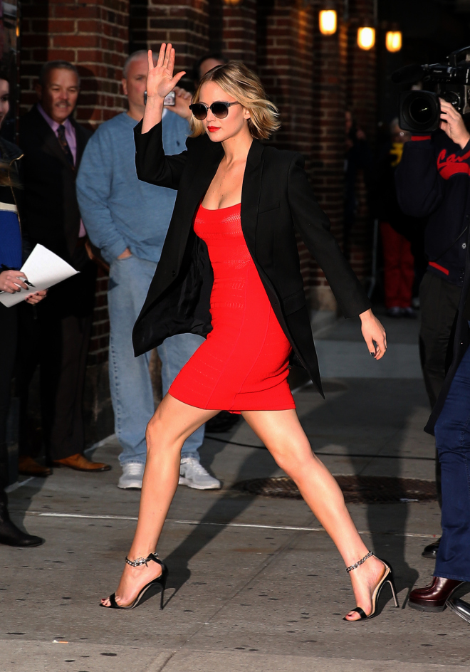 Actress Jennifer Lawrence, wearing a red dress, jacket and strappy sandals, arrives at 'The Late Show with David Letterman' on November 12, 2014 in New York City