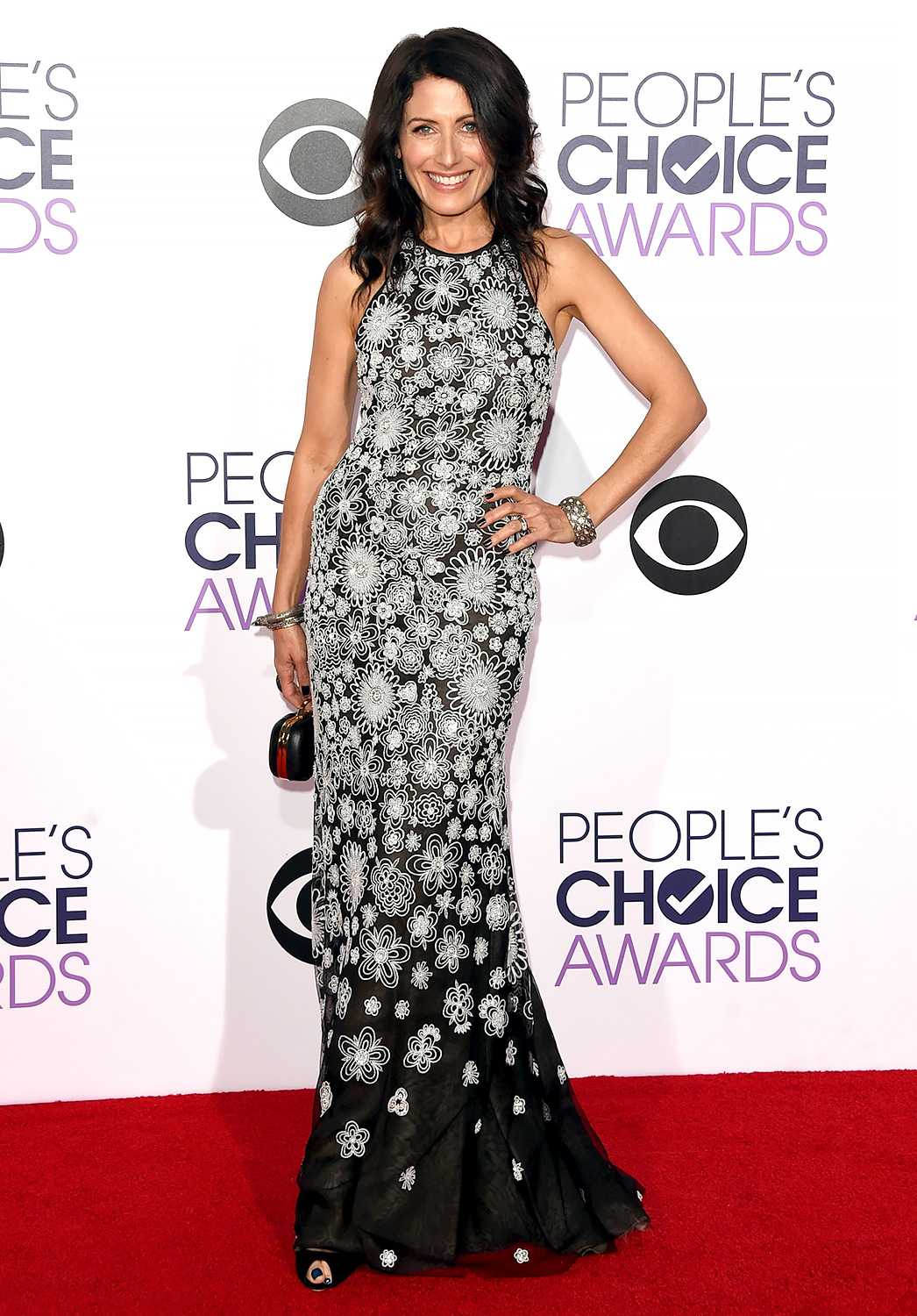 Lisa Edelstein in a sleeveless Naeem Khan Resort 2015 black & white floral beaded trumpet gown which she styled with a small clutch and bangles.