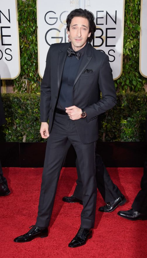 Adrien Brody in all black suit with a bow tie