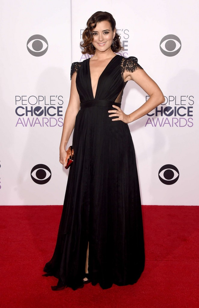Cote de Pablo in a black gown that has a center front split a black center front split gown with a v-neckline and a lace cape sleeves & back panel. She styled her look with a gold clutch, and a pair of black sandals