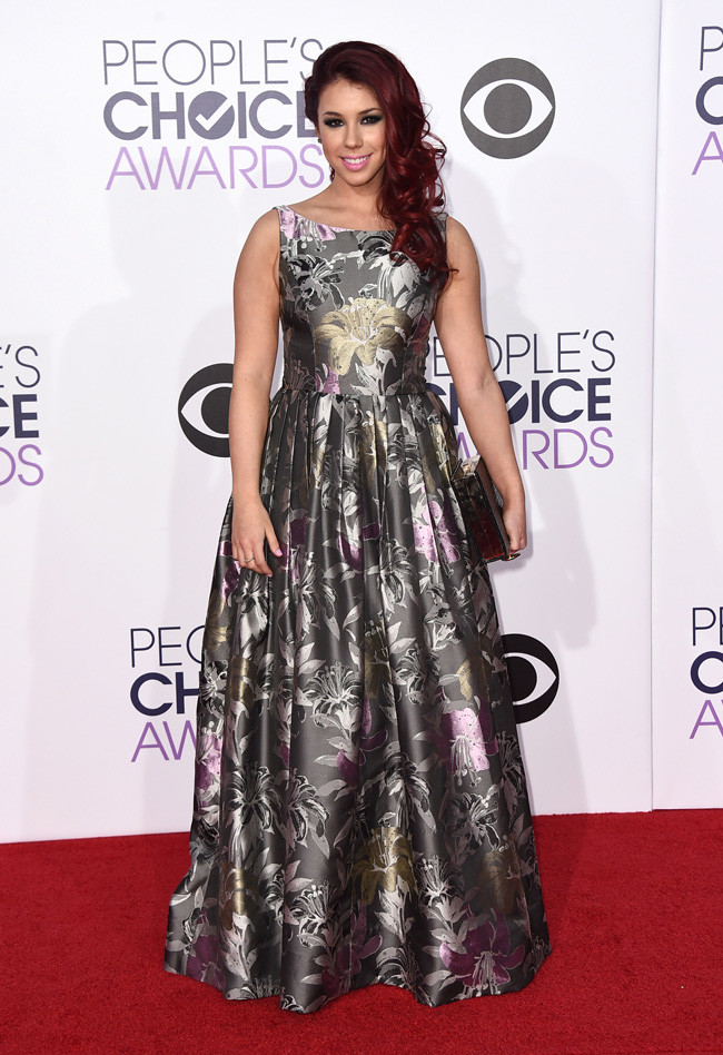 Jillian Rose Reed in a sleeveless silver floral gown style with a black clutch
