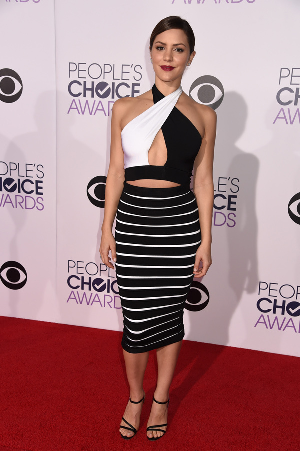 Katharine McPhee in a black & white Balmain dress that a has crisscross cut-out top and a stripe skirt which she styled with black sandals