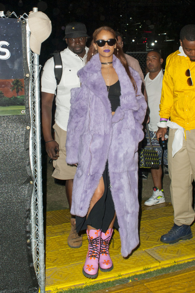 Rihanna wears a full length purple fur coat and pink boots in the desert as she smokes a funny looking cigarette and watches a concert at the Coachella Music Festival in Indio