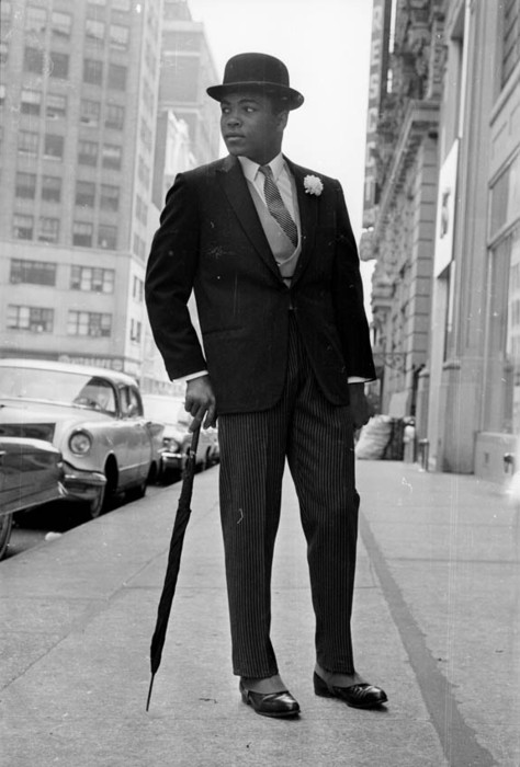 26th May 1963: American Heavyweight boxer, Cassius Clay (later Muhammad Ali), in New York, dressed like a city gent in a suit and a bowler hat and carrying an umbrella. (Photo by Express/Express/Getty Images)