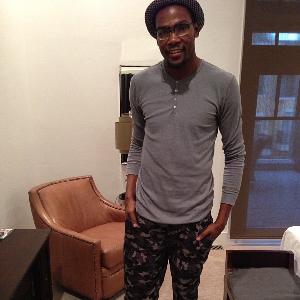 Durant in a camo-printed pants with a fitted grey henley and a bolo hat