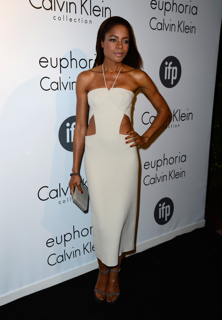 Naomie Harris in an off-white Calvin Klein halter dress with cut-outs at the waist, from the Resort 2013 collection. CK accessories including a white box clutch and grey strappy sandals