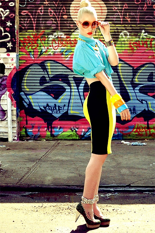 Iggy Azalea in a Yellow and Black Pencil Skirt. Turquoise Blouse. Chunky Bangles. Retro Sunglasses.